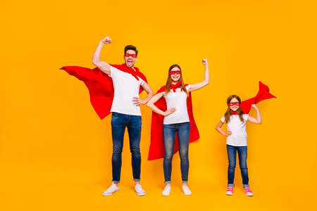 Mom dad and little foxy lady playing cartoon characters wear superhero capes isolated yellow background