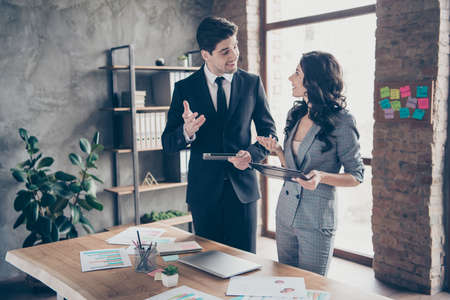 Photo of two business people partners share startup details standing workstation office dressed formal wear suits