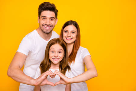 Photo of daddy mommy and small foxy lady making heart figure with hands wear casual outfit isolated yellow background Stock fotó