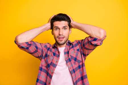 Photo of scared stunned man in stupor having no idea what to do with what he sees while isolated with yellow background