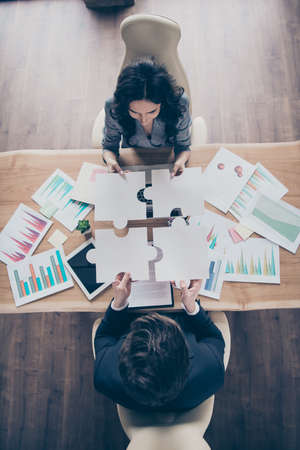 High angle view vertical photo of two partners putting difficult puzzle pieces together above workshop table Banco de Imagens