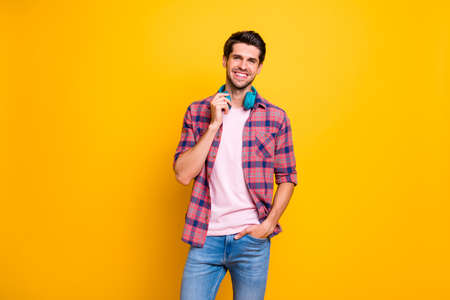 Photo of enjoying rejoicing man overjoyed with new earphones sound heard even when device is not put on while isolated with yellow background