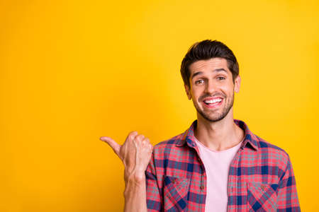 Photo of handsome model man drawing your attention to something away from him while isolated with yellow background