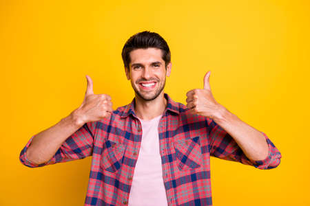Photo of joyful man sending you double thumb up in order to prove his right about new car while isolated with yellow background