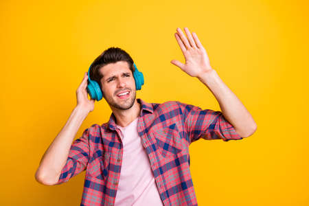 Photo of overjoyed listening man having been distracted from all problems with music while isolated with yellow background