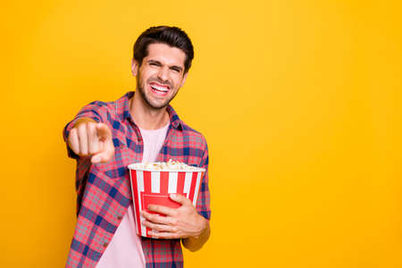 Photo of cheerful laughing rejoicing guy watching comedy movie with friends while isolated with yellow background
