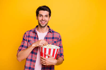 Photo of enjoying man watching his favorite movie and eating pop corn while isolated with yellow background