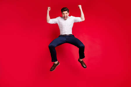 Full length body size photo of overjoyed strong victorious man having won something while isolated with red background