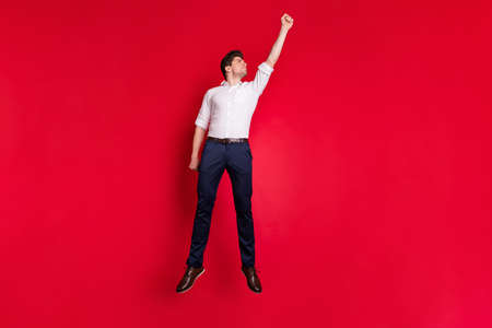 Full length body size photo of serious strong man pretending to be superhero stretching up while isolated with red background