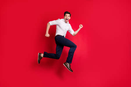 Full length body size photo of quickly running man hurrying up urgently while isolated with red background Zdjęcie Seryjne