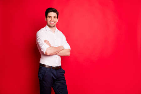 Photo of joyful interesting man being entrepreneur employing people to his large company while isolated with red background