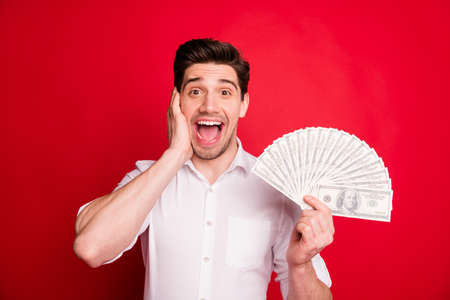 Photo of incredible income of shocked stunned man who does not understand what is going on while isolated with red background Zdjęcie Seryjne