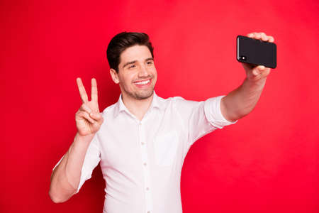 Photo of handsome trendy man taking selfie showing you v-sign while isolated with red background 写真素材