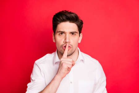 Close-up portrait of his he nice attractive focused serious guy showing shh sign keep my secrecy isolated over bright vivid shine red background