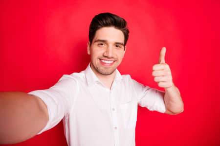 Self portrait of cheerful positive brunet man showing you thumb up sign to recommend something while isolated with red background Imagens