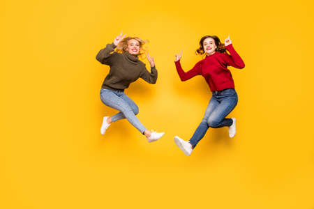 Full length photo of cute ladies jumping high showing v-signs wear knitted pullovers isolated yellow background