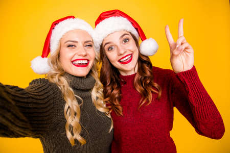 Pretty two ladies taking festive self photos showing v-sign wear knitted jumpers and santa hats isolated yellow background Reklamní fotografie