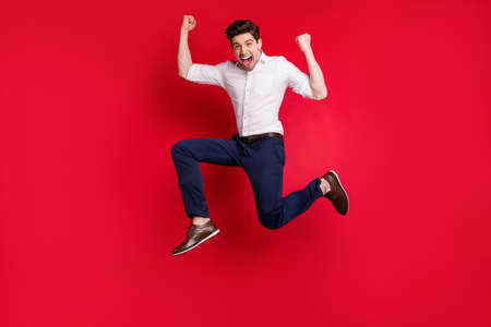 Photo of cheerful overjoyed excited ecstatic man running with happiness of having reached his goal while isolated with red background