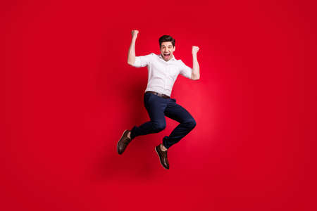Full length body size photo of man jumping with happiness dressed formally while isolated with red background 写真素材