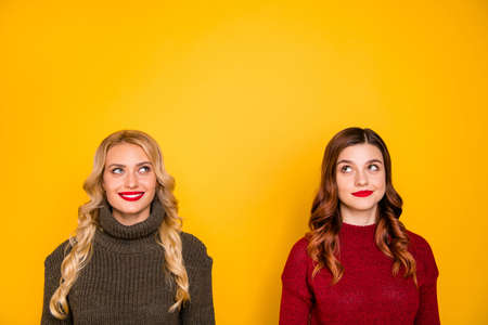 Pretty two ladies look empty space wonder if there are new rumours wear knitted jumpers isolated yellow background Zdjęcie Seryjne