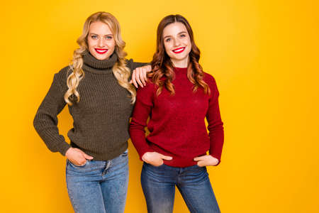 Photo of two amazing ladies standing close wear knitted sweaters isolated yellow background 版權商用圖片