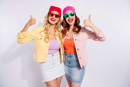 Photo of two pretty ladies raising thumbs up wear sun specs casual clothes isolated white background