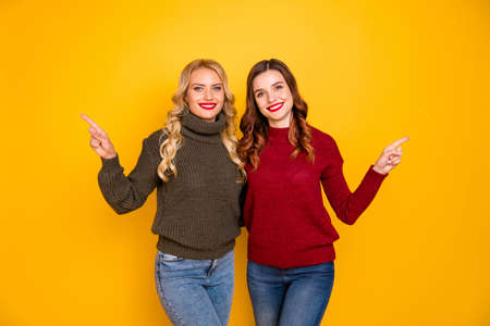 Pretty two ladies indicating finger empty space wear knitted pullovers isolated yellow background Stok Fotoğraf - 129250757