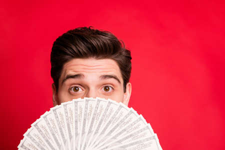 Photo of man looking out of money fan successful having received salary while isolated with red background