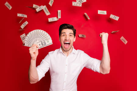 Foto van brunet witte rijke rijke man die geniet van zijn succes terwijl hij geïsoleerd is met rode achtergrond