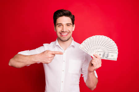 Photo of excited man showing pointing symbol at his money he just received while isolated with red background