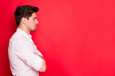 Profile side view portrait of his he nice attractive well-groomed content guy top ceo boss chief director copy empty blank place space folded arms isolated over bright vivid shine red background