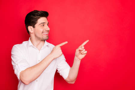 Close-up portrait of his he nice lovely cheerful cheery positive glad content guy student employee pointing two forefingers aside ad advert tips feedback isolated on bright vivid shine red background