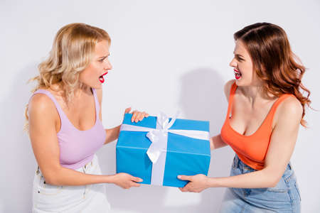 Photo of two ladies cant share one giftbox yelling each other wear casual clothes isolated white background Stock Photo