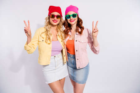 Photo of two pretty ladies showing v-sign symbols wear sun specs casual clothes isolated white background
