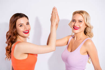 Closeup photo of two pretty ladies clapping hands wear casual tank-tops isolated white background