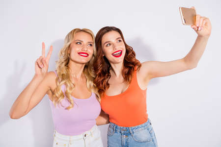 Pretty ladies holding telephone hands making selfies showing v-sign wear casual tank-tops isolated white background