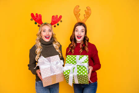 Photo of two amazed ladies received big giftboxes for xmas wear sweaters and head horns isolated yellow background