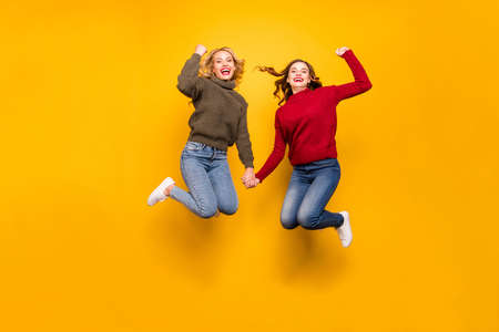 Full length photo of cute ladies jumping high celebrating win wear knitted sweaters isolated yellow background
