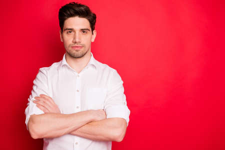 Portrait of concentrated entrepreneur crossing his hands wearing white shirt isolated over red background 写真素材