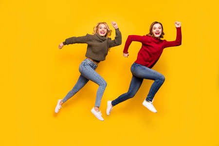 Full body photo of two ladies jumping high hurrying shopping wear knitted sweaters isolated yellow background