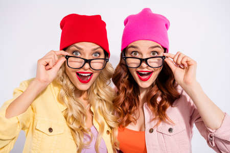 Photo of two pretty overjoyed ladies wear specs casual clothes isolated white background Фото со стока