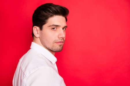 Close up photo of unshaven stubbled man epically looking into camera while isolated with red background Фото со стока - 129250929