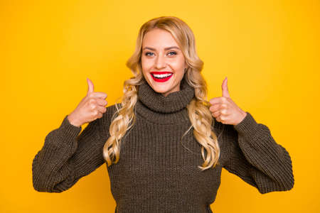 Photo of amazing lady raising thumbs up approving good news wear warm sweater isolated yellow background