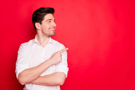 Portrait of his he nice attractive cheerful cheery content guy employee pointing forefinger aside ad advert tips feedback sale discount solution isolated over bright vivid shine red background Stok Fotoğraf
