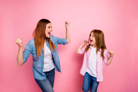 Profile side photo of cheerful people raising their fists screaming yeah wearing jeans denim shirt isolated over pink background