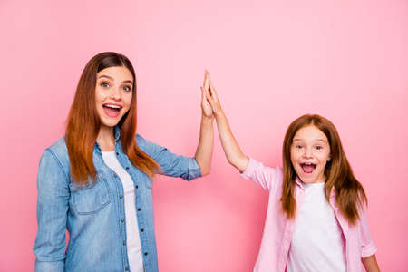 Portrait of excited ladies with long haircut clapping hands screaming yeah wearing denim jeans shirt isolated over pink background