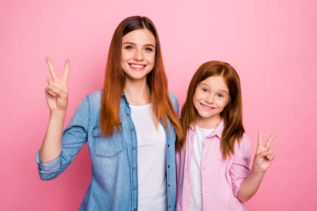 Portrait of cheerful girls with long hair making v-signs wearing denim jeans shirts isolated over pink background