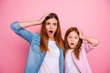Portrait of impressed ginger haired girls with long hairstyle staring screaming wearing denim jeans shirt isolated over pink background Zdjęcie Seryjne