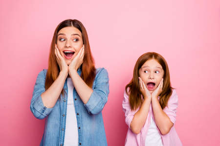 Portrait of impressed ladies touching their cheeks shouting wearing denim jeans shirt isolated over pink background Zdjęcie Seryjne