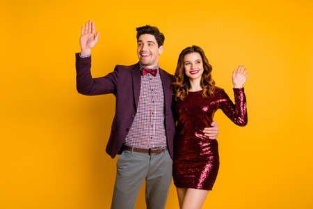 Portrait of his he her she nice-looking attractive elegant smart cheerful friendly people spending holiday waving greetings isolated over bright vivid shine yellow background 版權商用圖片